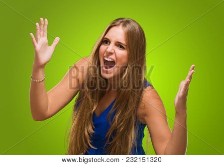 Portrait Of A Young Woman Yelling against a green background