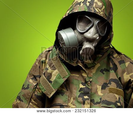 angry soldier wearing a gas mask against a green background