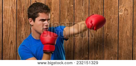Young man wearing boxing gloves and punching against a wooden background