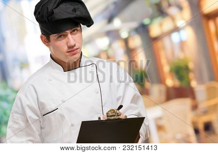 Portrait Of A Young Chef With Writing Pad at a restaurant
