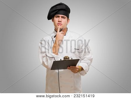 Young Chef With Writing Pad Thinking against a grey background