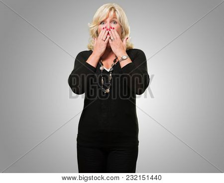 Scared Woman Covering Her Mouth against a grey background