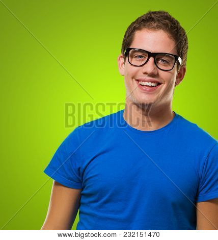 Happy young man wearing eyeglasses against a green background