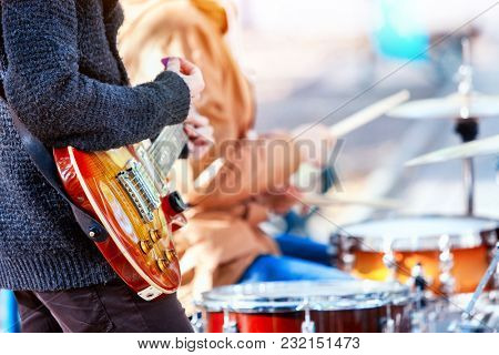 Festival music band. Hands playing on percussion instruments in city park. Drums with sticks closeup. Body part of male musicians. Sharpen is guitar and man hand. Hobby of adults.