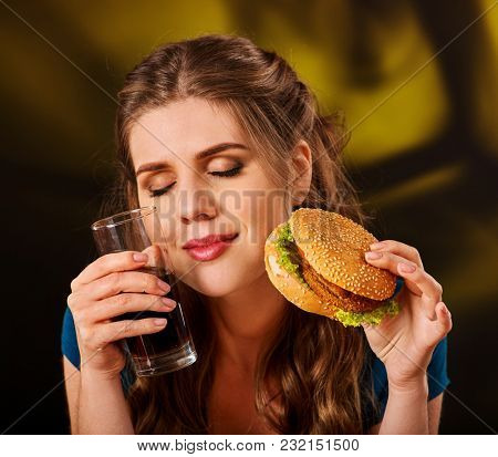 Woman eating french fries and hamburger. Student consume fast food on table. Girl drinks cola and dreams. Girl trying to eat junk. Advertise fast food on isolated. Diet without restrictions.