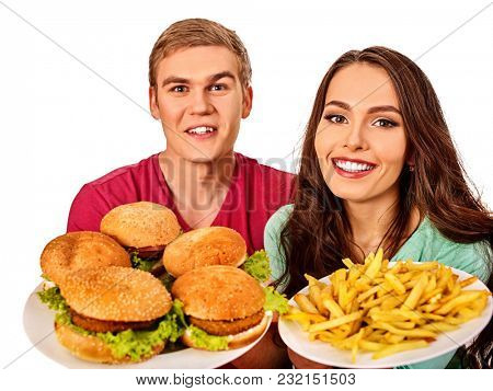 Couple eating fast food. Man and woman eat hamburger with ham. Friends holding two burder junk on white background isolated. People try to feed each other. Health problems due to malnutrition.