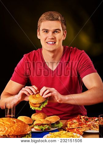 Man eating french fries and hamburger with pizza. Portrait of student consume fast food on table. Dark background. Cook teaches to cook and shares recipes.