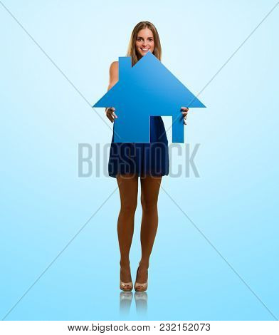 Young Woman Holding House Model Isolated On Blue Background