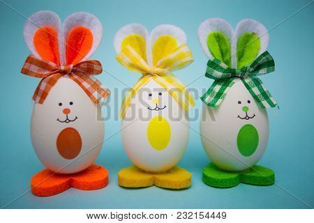 Multicolored Funny Eggs In The Form Of Cute Bunny On Blue Background. Happy Easter. Festive Decorati