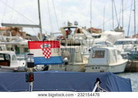 Croatian Flag In Front Of The Marina Full Of Small Boats And Yachts