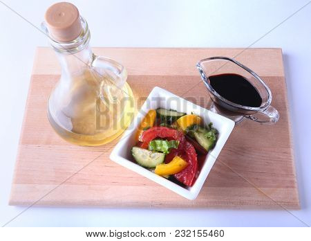 Fresh Vegetable Salad With Tomato, Cucumber, Bell Pepper, Lettuce Leaf In White Bowl, Olive Oil And