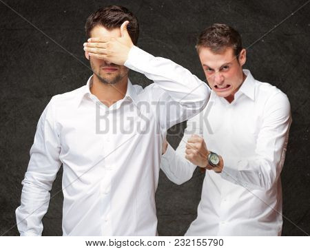 Young Man Covering Eyes And Aggressive Man Standing Behind On Black Background