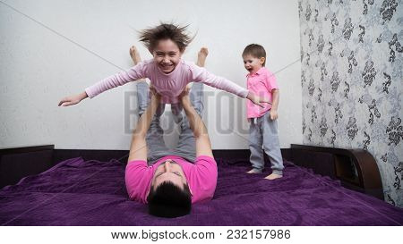 Father Lies On The Back And Holds Daughter Above Themselves. Girl Raised Hands Like Wings And Smilin