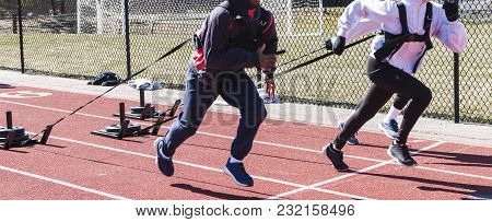 High School Track And Field Runners Sprint Down The Track While Pulling Sleds With Weights On Them.