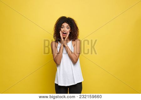 Smiling Beautiful Young African American Woman In White T-shirt Posing With Hands On Chin. Studio Sh