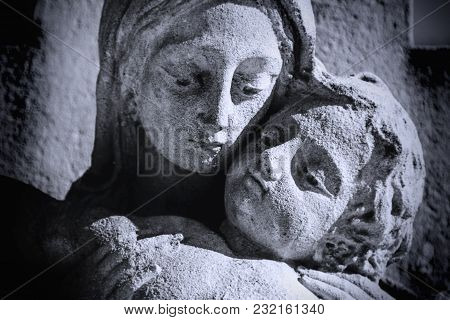Close Up Of Ancient Statue Virgin Mary Holding A Baby Jesus On A Cross As Symbol Of Empathy And Suff