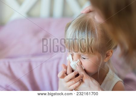 Child With Runny Nose. Mother Helping To Blow Kid's Nose With Paper Tissue. Seasonal Sickness