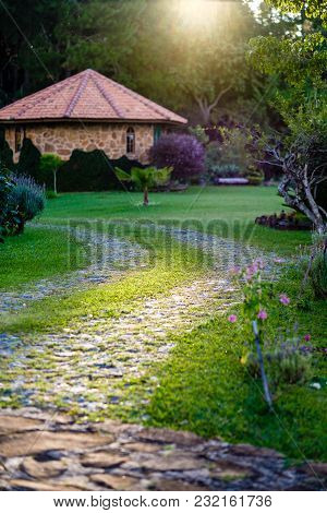 Rocky Pathway Leading To Wooden Structure, Forest In Background. Grass Sorroundings. Light Rays Gold