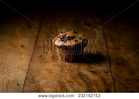 Chocolate Chip Muffin Or Cupcake On Wood Table, Side Lighting, Product Photography. Close Up, Dark S