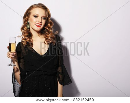 Young celebrating woman black dress. Beautiful model portrait isolated over studio background hold wine glass.
