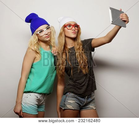 two hipster girls friends taking selfie with digital tablet, studio shot over gray vackground