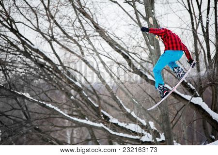 Image of sportive man wearing helmet jumping on snowboard against background of winter trees