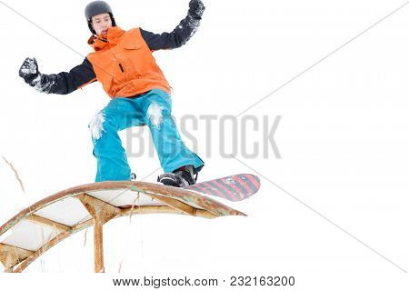 Picture of sportive man skiing on snowboard with springboard