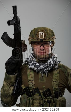 Image of soldier in safety glasses with gun in his hand