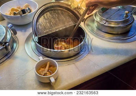 Hand Holding Spoon Of Sour Soup From Stainless Container In Salad Bar Area.