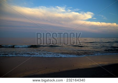 The Atlantic Ocean After Sunset With The Clouds And Sky Reflecting Off The Water And Shoreline