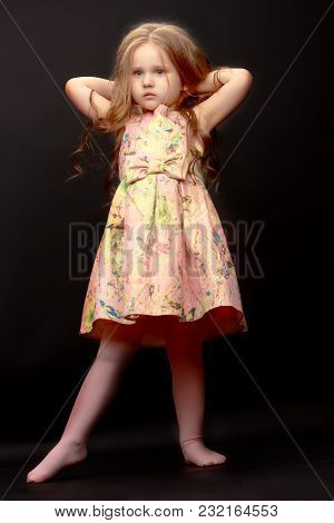 Beautiful Little Girl On A Black Background. Studio Photography
