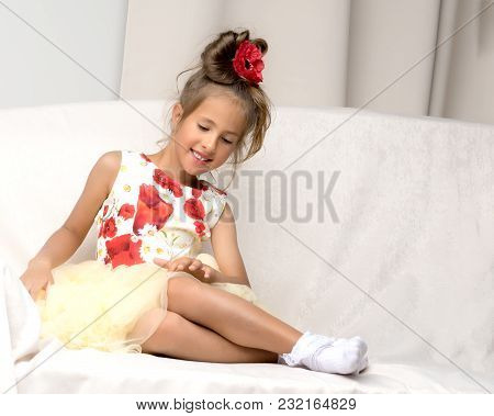 A Little Girl Is Sitting On The Couch In A Photo Studio. Isolated On White Background
