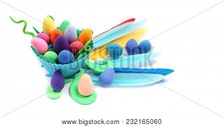 Easter. Abstraction from Plasticine. Easter decoration. Colored eggs and feathers on a white background