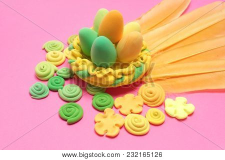 Easter decoration. Colored eggs and feathers on a pink background