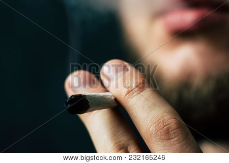 Cannabis Weed, A Joint In His Hands A Man Smokes . Smoke On A Black Background. Concepts Of Medical