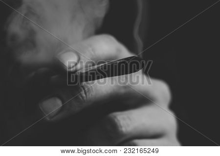 A Man Smokes Cannabis Weed, A Joint And A Lighter In His Hands. Smoke On A Black Background. Concept