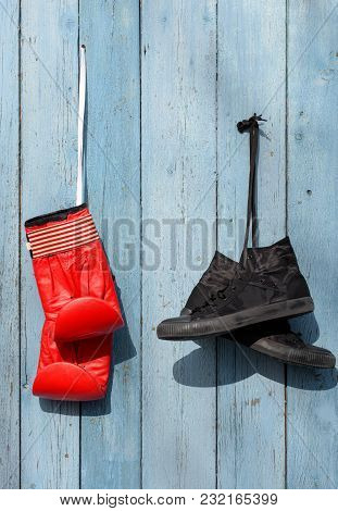 Black Textile Worn Sneakers And Red Leather Boxing Gloves Hanging On A Blue Wooden Wall