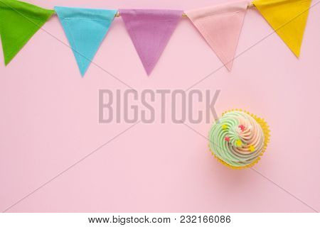 Pastel Cupcake And Colorful Bunting Party Flag On Pink Background With Copy Space For Text, Birthday