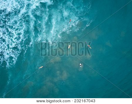 Surfers Swim To Big Wave Aerial Drone Above View. Group Of Surfers Swim In Blue Ocean Water