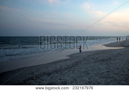A Child, Little Boy Standing On The Beach Along The Shoreline Of The Atlantic Ocean In The Evening A