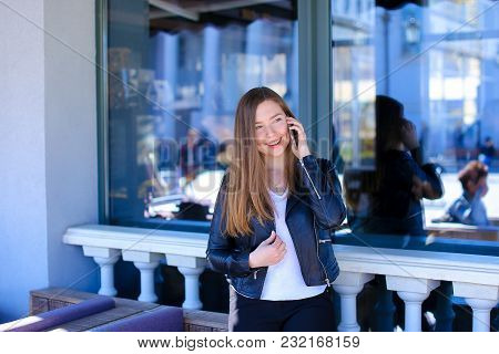 Young Female Person Talking By Smartphone At Cafe Near Window. Concept Of Communicating And Gadgets.