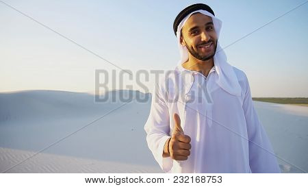 Portrait Of Emirate Male Advertising Agent Or Bank Employee Who, With Smile On Face, Attracts And Ad