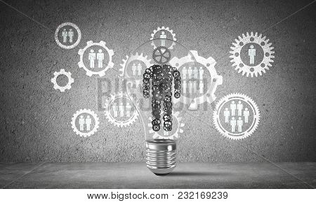 Lightbulb With Human From Gears Inside Placed Against Social Gear Structure On Grey Wall. 3d Renderi