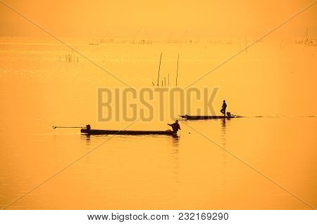 Fishermen On Boat In Silhouette Using Fishing Net To Fish In Rural Swamp During Sunset