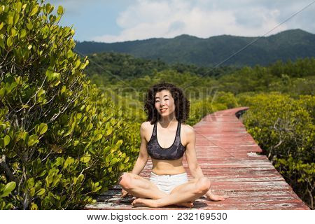 Young mixed race woman in a mangrove forest.