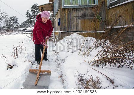 Elderly woman cleans the snow near rural home.