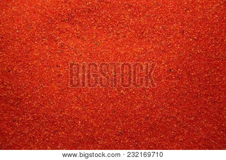 Texture Of A Colored Granular Sand Close Up. Red Grains