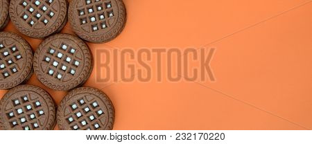 Detailed Picture Of Dark Brown Round Sandwich Cookies With Coconut Filling On An Orange Surface. Bac