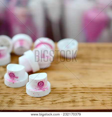 The Soiled Pink Nozzles From The Paint Sprayer Lies On A Wooden Plank On A Background Of A Many Dirt