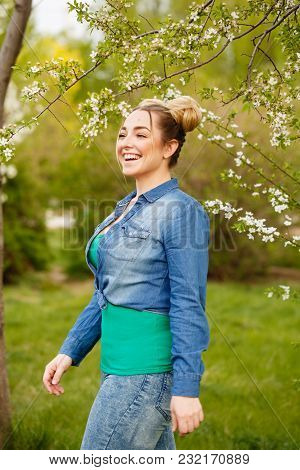 Young Attractive Girl Is Walking In The Spring Park And Smiling